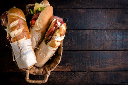 filled roll: Served sandwiches in the basket on wooden background with blank space Stock Photo
