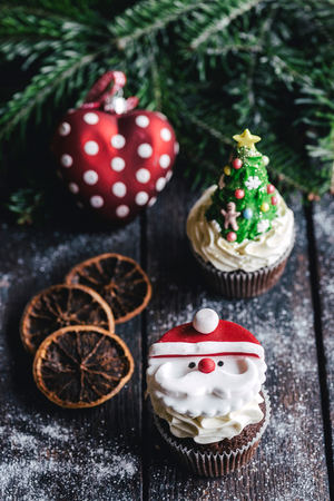 Santa Claus cup cake on wooden background,selective focus