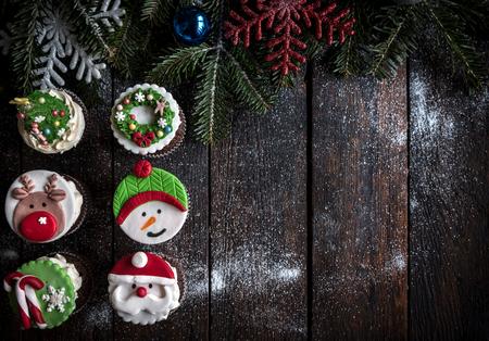 guirnaldas de navidad: Tortas de la taza con la decoración de Navidad en el fondo de madera con espacio vacío