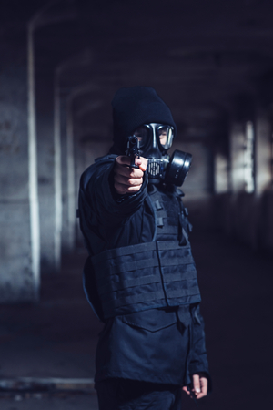 readiness: The terrorist with gas mask pointing gun,selective focus