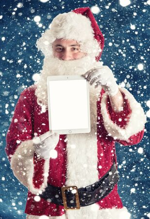 Santa holding tablet pc with blank screen photo