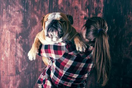 Female holding big English bulldog,friendship concept photo