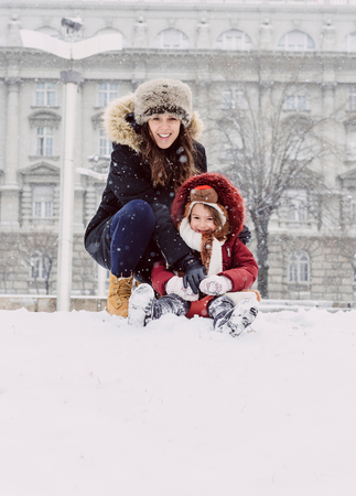 Mother and daughter playing on the snow photo