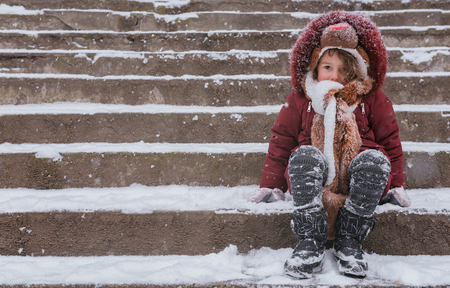 Sad child sitting on the stairs covered with snow  photo
