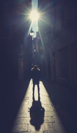 Silhouette of woman with big shadow on the street 写真素材