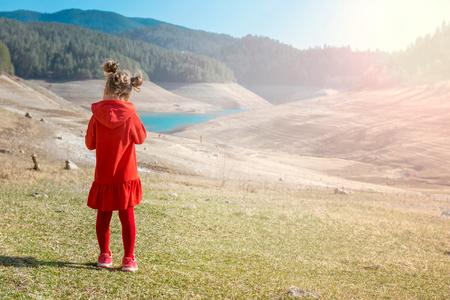 Little girl in red dress on meadow photo