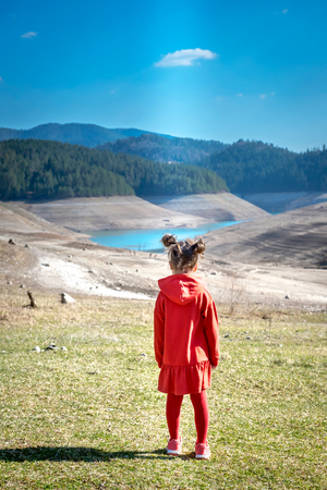 Little girl in red dress looking on landscape,selective focus photo