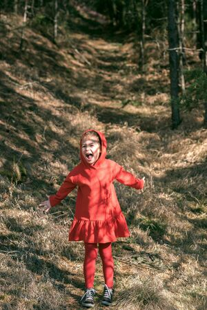 Portrait of scared little girl in the woods photo