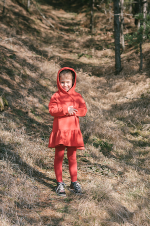 Little girl in the red dress posing in wood photo