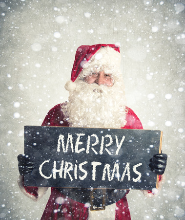 Santa Claus with blank chalkbord holding in his hands Stock Photo