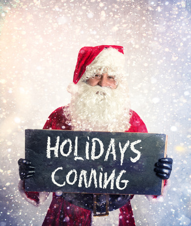Santa Claus with chalkbord with holidays coming sign in his hands Stock Photo