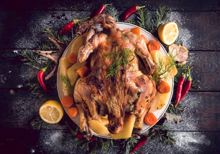 Whole roasted turkey with baked potatoes served on the plate Stock Photo