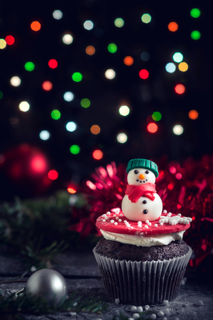 guirnaldas de navidad: Snowman on the cupcake with Christmas decoration,selective focus Foto de archivo