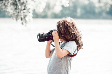 Little child photographing with dslr camera
