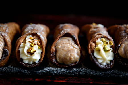Close up to traditional italian cannoli with ricotta and chocolate,selective focus
