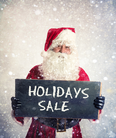 Santa Claus with chalkbord with happy holidays sale in his hands
