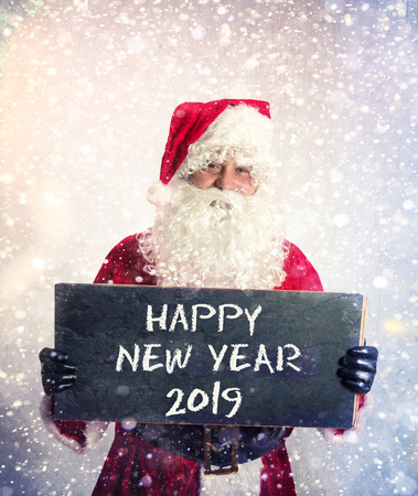 Santa Claus with chalkbord with happy new year 2019 sign in his hands