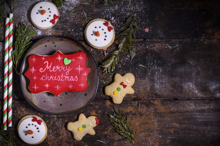 Merry Christmas gingerbread cookies on the wooden background with blank space