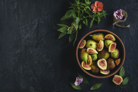 Raw figs served in the bowl on the dark background with blank space,selective focus
