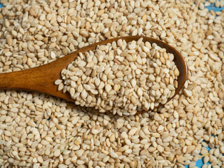 white sesame seeds, sesame seeds in a wooden spoon on an old rustic background close-up