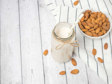 nuts almonds and almond milk on a white wooden table