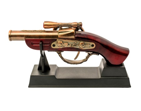 Photo of copy of an old gun with wooden handle on a stand isolated on white background