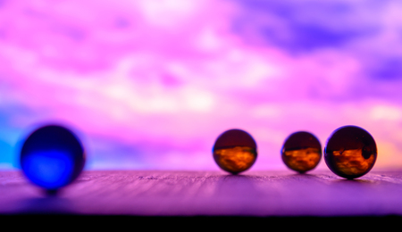 Photo of many color glass balls on wooden board on blurred background