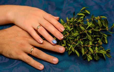 Foto van twee handen met mooie trouwringen en groene bladeren op blauwe achtergrond