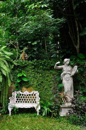 escultura romana: Silla de metal blanco y la escultura romana en jard�n natural