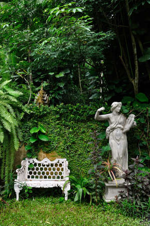 White metal chair and roman sculpture in natural garden Stock Photo