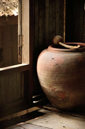 splotchy: Dirty and shadowy rough earthen jar and dipper at corner in wood house  Stock Photo