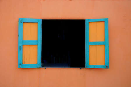 Wooden blue window on orange wall of coffee shop in countryside  Stock Photo