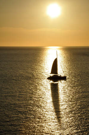 A silhouette of sailboat and shadow from the shining sunset at Promthep Cape, Phuket, Thailand  photo