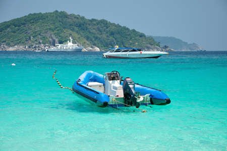 Motor boat floating on clear blue andamand sea, Thailand  Stock Photo