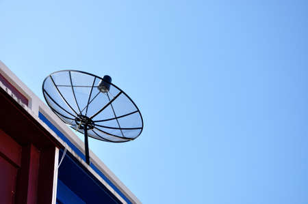 Satellite dish antenna for television on house roof, Thailand