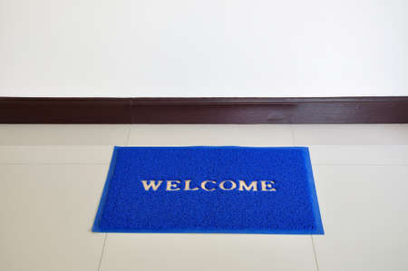 Blue welcome anti-slip door mat on the floor  photo