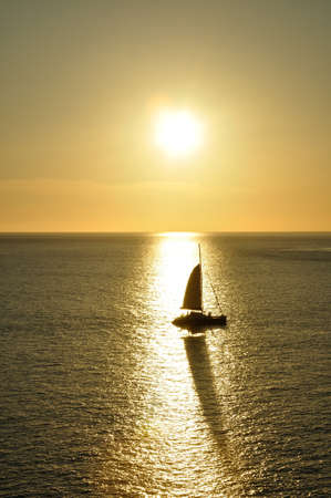 Silhouette of sailboat and shadow reflection from sunset at Promthep cape, Phuket Thailand  photo