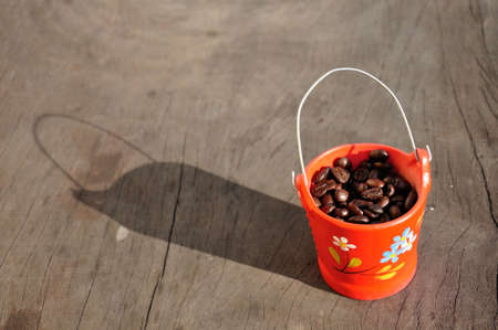 Coffee beans in mini orange bucket with morning light on wooden table