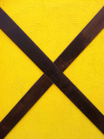 backdrop: yellow exposed concrete wall with cross wood.