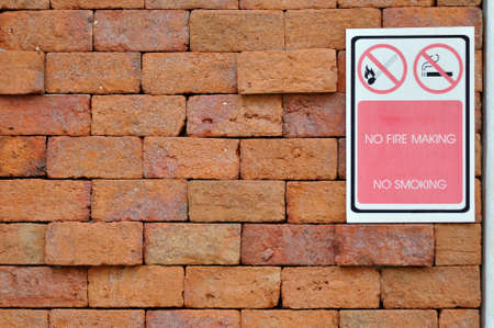 No smoking and fire making sign on the red brick wall  photo