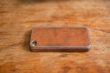木製のテーブルの上の本革カバー付き携帯電話。 写真素材