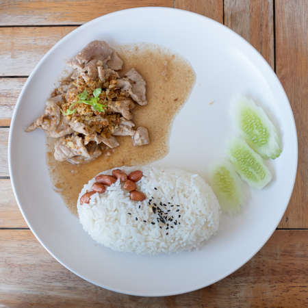 Rice with fried sliced pork with garlic and black pepper. photo