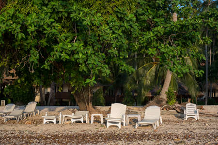 white beach chairs arranged in front of beach for sunbathe at koh ngai resort, Thailand.