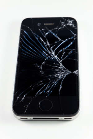 Broken screen mobile smartphone isolated on white background. Stock Photo