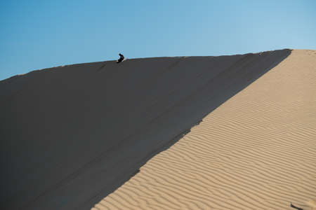 people sitting at the golden sand dune at Muine, Vietnam.