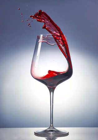 Red wine splashing in a glass on gradient background