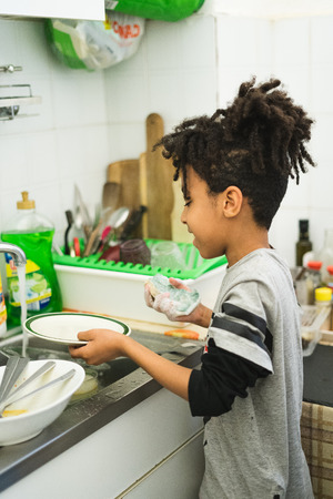 Afro American child has fun doing household chores. Wash the dishes in the sink. Banque d'images - 108087676