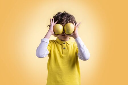Kid hiding his eyes with two apples. Fruit and healthy fruit diet for children concept