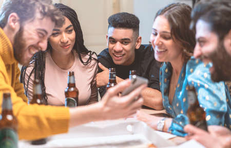 Group of smiling young people watching video on smartphone and drinking beers in a house. Multiracial friends having fun using smartphone, social network apps and new technologies concept.