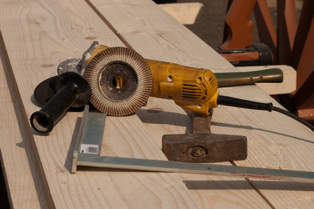 rotates: Electric grinder lying on a wooden plank. The grinder is leaning against abrasive mop. At the forefront of steel angle. Under grinder worn hammer. Stock Photo